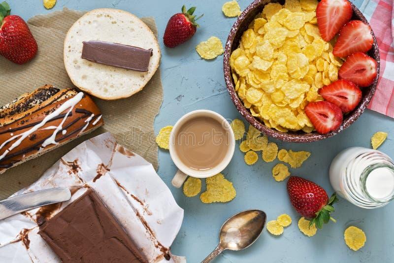 Petit déjeuner, flocons d'avoine avec les fraises fraîches et lait, beurre de chocolat avec les pâtisseries fraîches sur un fond  photo stock