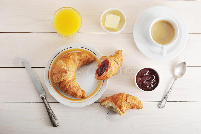 Petit déjeuner français - croissant, confiture, beurre, jus d'orange et coff images stock