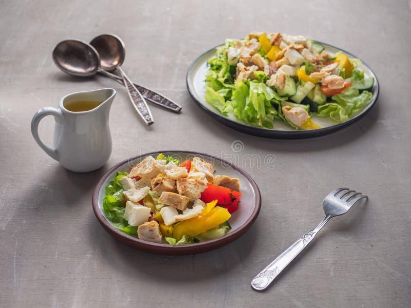 Petit déjeuner léger de salade de César sur deux tarekkas, se tenant sur une table, des couverts et une saucière en bois avec de  photos libres de droits