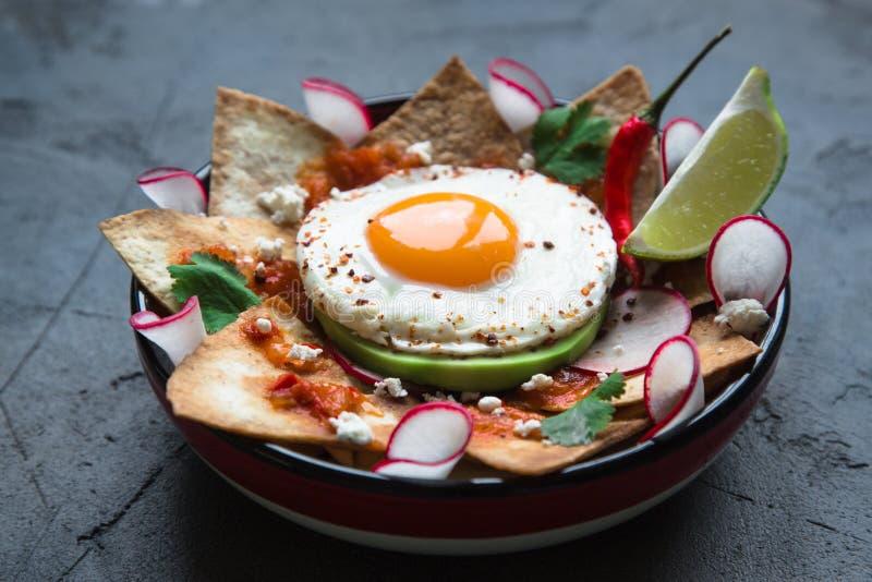 Petit déjeuner mexicain : chilaquiles avec l'oeuf, l'avocat et le plan rapproché de légumes d'un plat photo stock