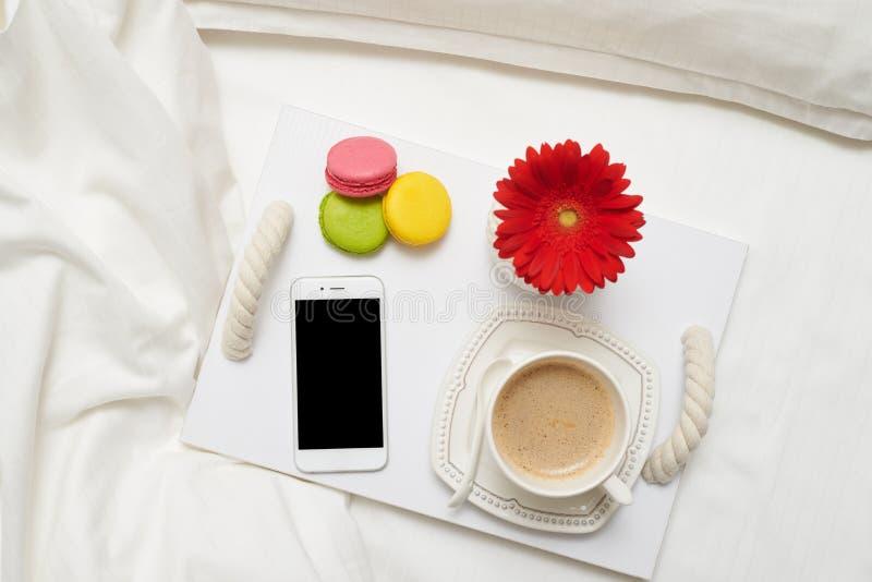 Petit déjeuner romantique avec du café, les macarons et le téléphone portable sur le TR images stock
