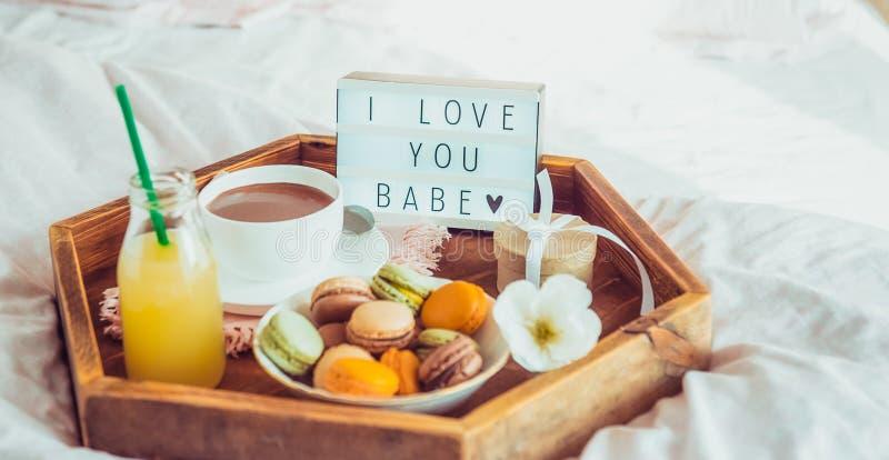 Petit déjeuner romantique dans le lit avec je t'aime le texte de bébé sur la boîte allumée Tasse de café, de jus, des macarons, d images stock