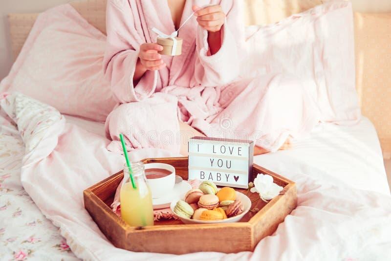 Petit déjeuner romantique dans le lit avec je t'aime le texte sur la boîte allumée, le café, les macarons sur le plateau en bois  images libres de droits