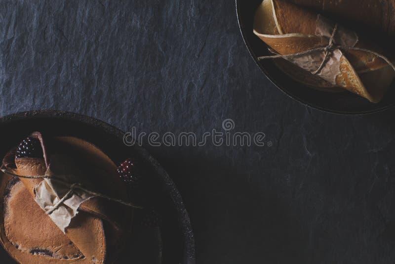 Petit déjeuner rustique avec des crêpes de chocolat dans des casseroles de friture rouillées sur le DA photographie stock