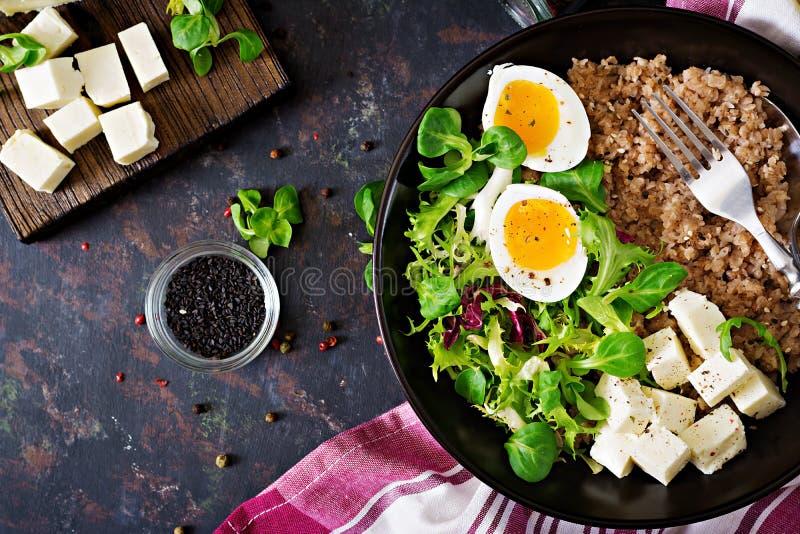 Petit déjeuner sain avec le gruau d'oeufs, de fromage, de laitue et de sarrasin sur le fond foncé Nutrition appropriée Carte diét photos stock