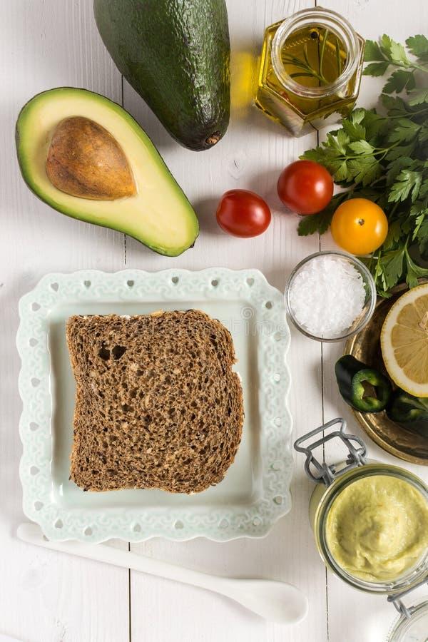 Petit déjeuner sain avec le guacamole frais de diffusion d'avocat photographie stock libre de droits