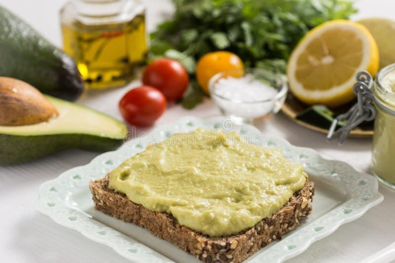 Petit déjeuner sain avec le guacamole frais de diffusion d'avocat image stock