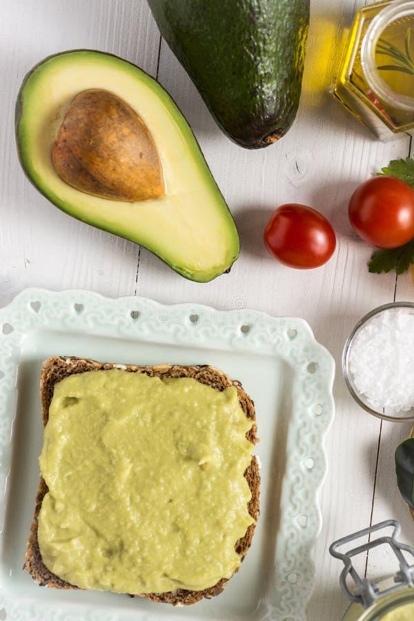 Petit déjeuner sain avec le guacamole frais de diffusion d'avocat photo stock