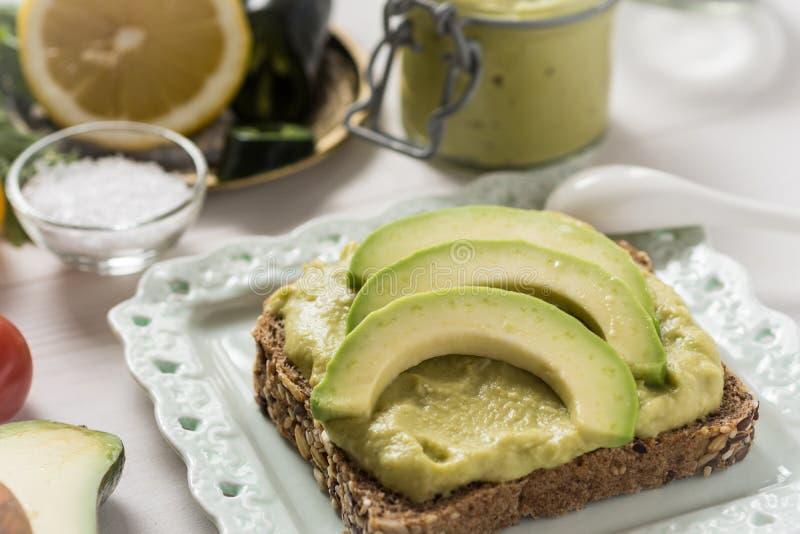 Petit déjeuner sain avec le guacamole frais de diffusion d'avocat photos stock