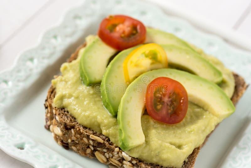 Petit déjeuner sain avec le guacamole frais de diffusion d'avocat photographie stock