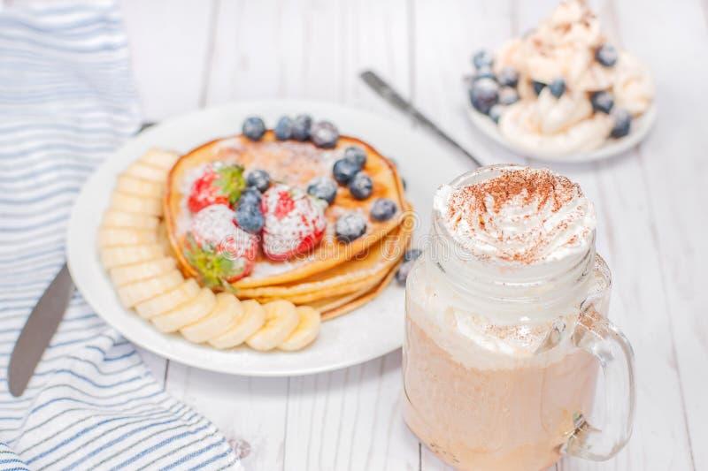 Petit déjeuner sain, café ou cappuccino et crêpes faites maison avec les baies et la banane fraîches photo stock