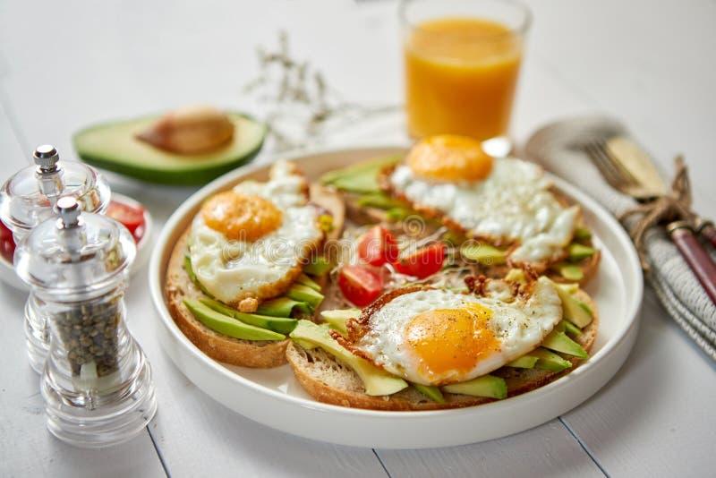 Petit déjeuner sain délicieux avec les sandwichs coupés en tranches à avocat avec l'oeuf au plat image stock