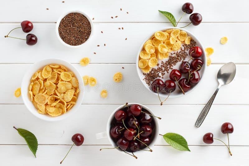 Petit déjeuner sain d'été avec les flocons d'avoine, le yaourt grec, la merise et les graines de lin dans la cuvette sur la table photographie stock