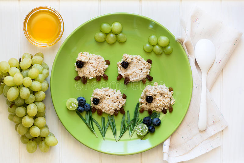 Petit déjeuner sain de bébé : les moutons de farine d'avoine ont décoré des baies image libre de droits