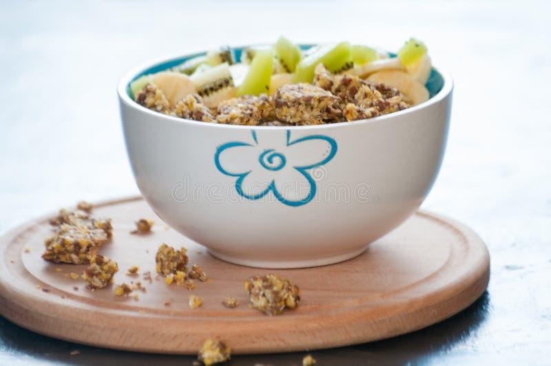 Petit déjeuner sain de granola, de kiwi, de banane et de yaourt dans une cuvette sur un plateau en bois Régime de forme physique  image stock