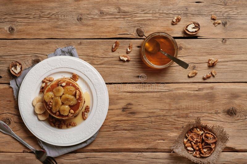 Petit déjeuner sain des crêpes avec du miel, des écrous et b caramélisé photographie stock libre de droits