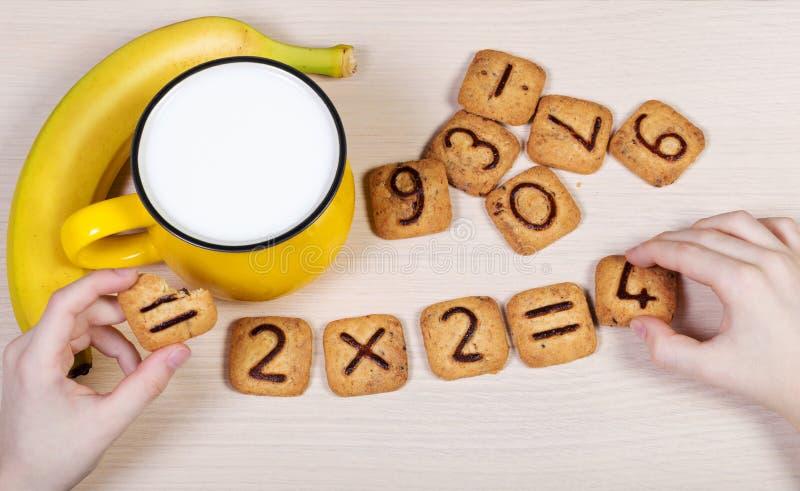 Petit déjeuner sain pour des écoliers Lait, banane et drôle photo stock