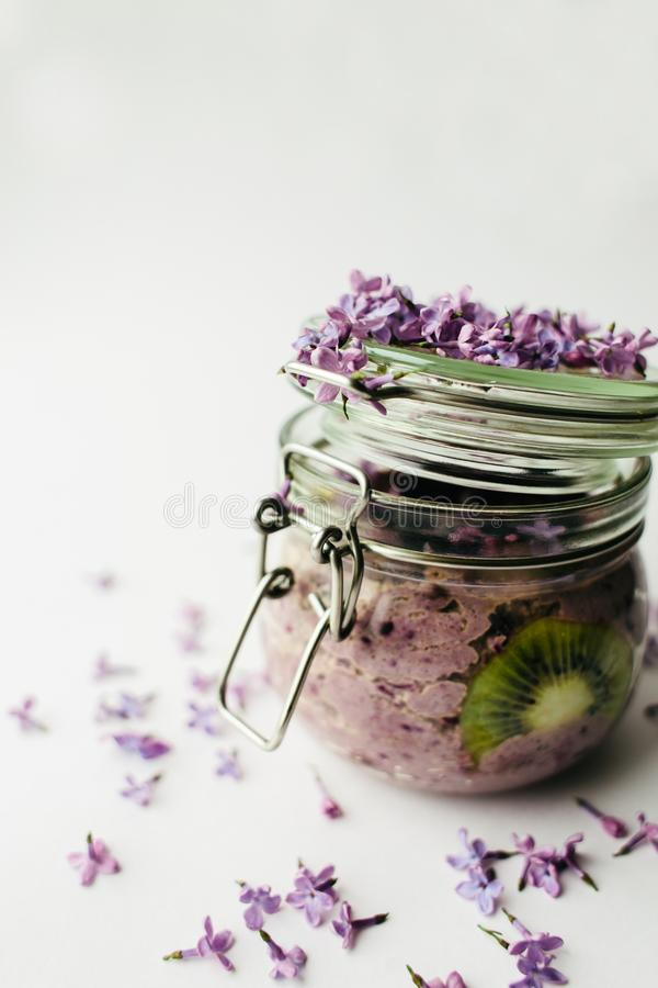 Petit déjeuner sain pourpre de smoothie dans un pot en verre avec les fleurs lilas photo libre de droits