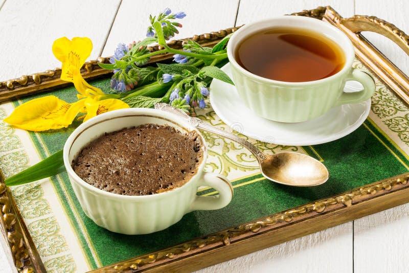 Petit déjeuner sur un plateau : un petit gâteau de chocolat et une tasse de thé image stock
