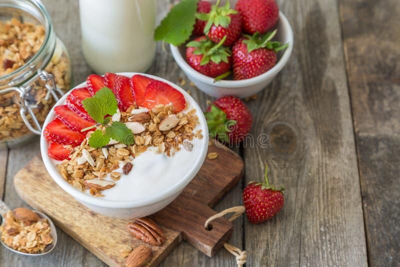 Petit déjeuner - yaourt avec la granola et les straberries photos stock