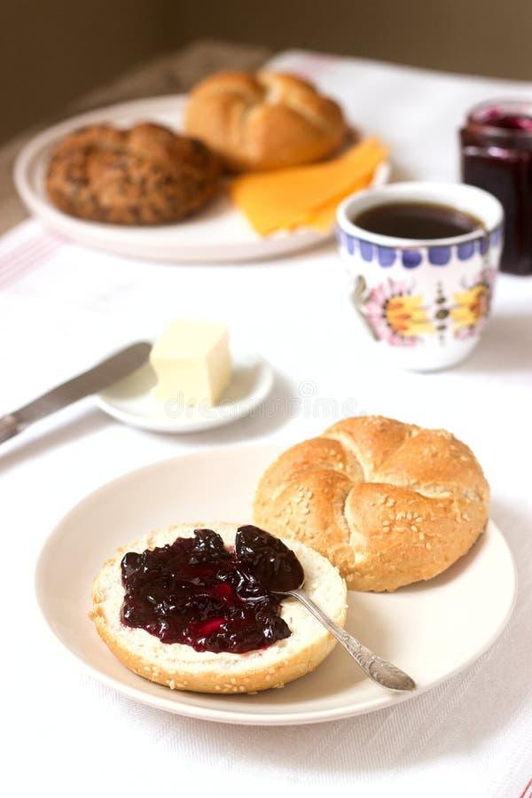 Petit d?jeuner avec les petits pains de Kaiser, la confiture de groseille, le beurre et le fromage et le th? photos libres de droits