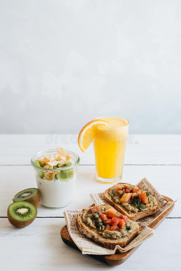 Petit d?jeuner d?licieux sur la table blanche Le verre de jus d'orange, de yaourt de kiwi et de pains grill?s de vegan photographie stock libre de droits