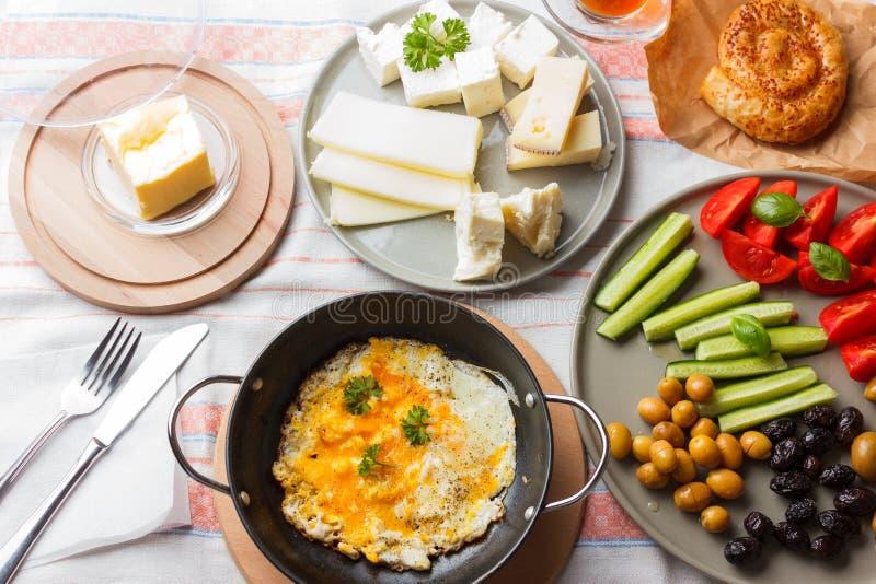 Petit d?jeuner turc traditionnel - oeufs au plat, l?gumes frais, olives, fromage, g?teau et th? photos libres de droits
