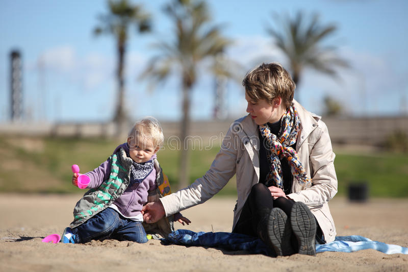 Petit descendant et mère jouant sur le sable photo stock
