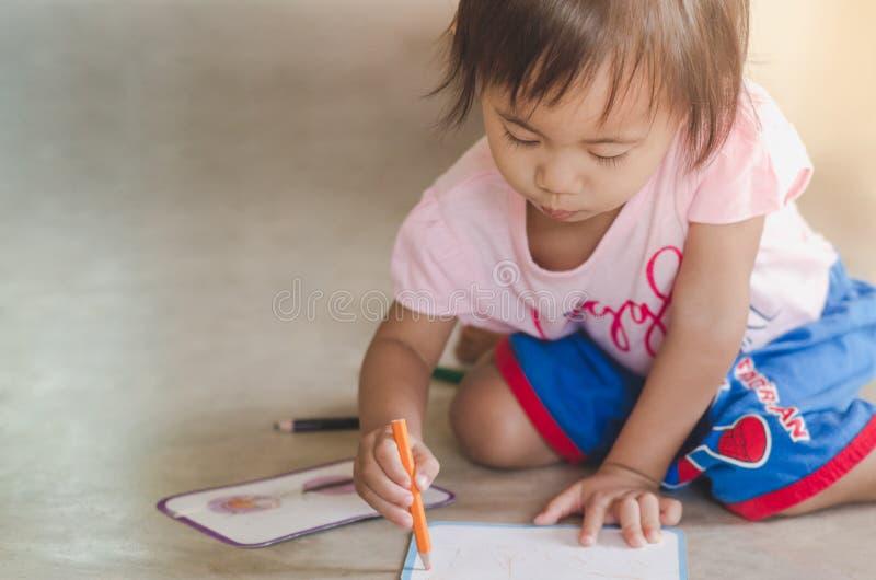 Petit dessin de bébé avec le crayon de couleur sur le papier tandis que sittin photographie stock