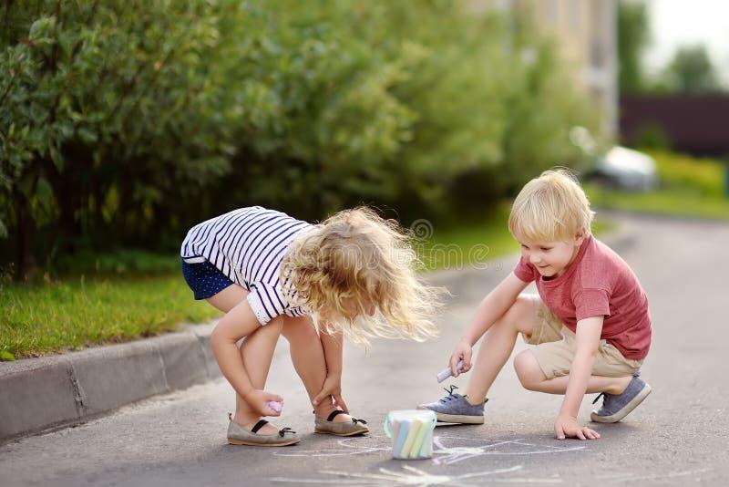 Petit dessin heureux de garçon et de fille avec la craie colorée sur l'asphalte photos stock