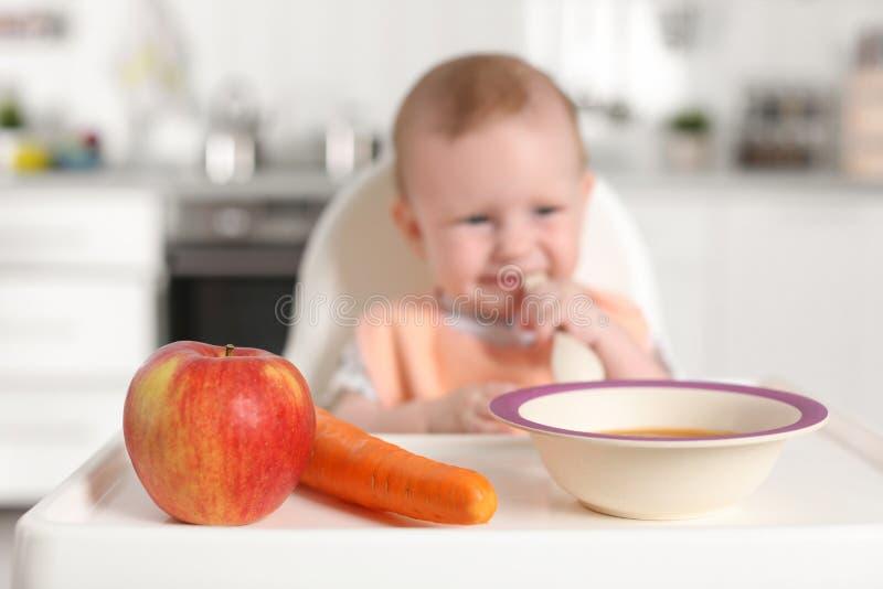 Petit enfant adorable prenant le petit déjeuner dans le highchair à l'intérieur images stock