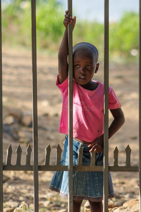 Petit enfant africain tenant la barrière proche photo libre de droits