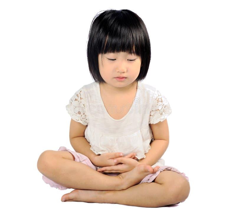 Petit enfant asiatique faisant la méditation dans la pratique en matière de bouddhisme images stock