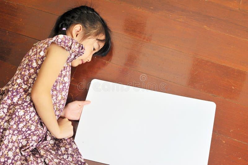 Petit enfant asiatique fixant sur le fond en bois avec un b photographie stock