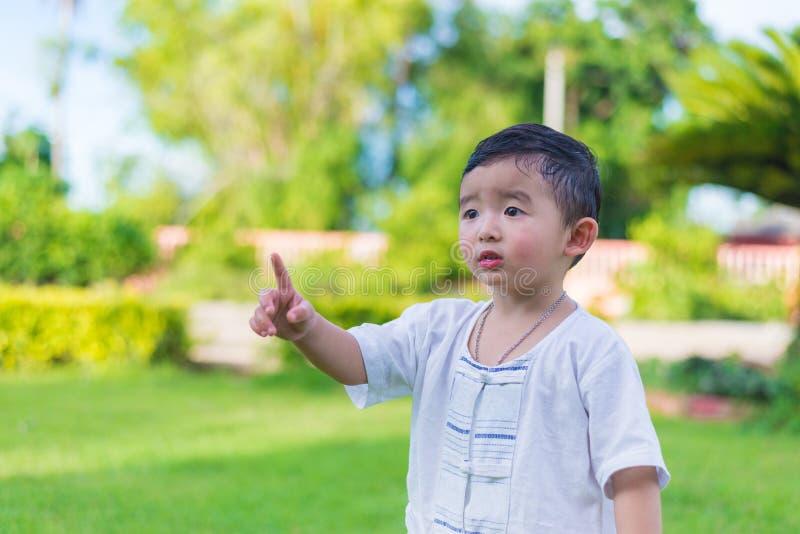 Petit enfant asiatique indiquant par des doigts quelque chose ou la Co vide image stock
