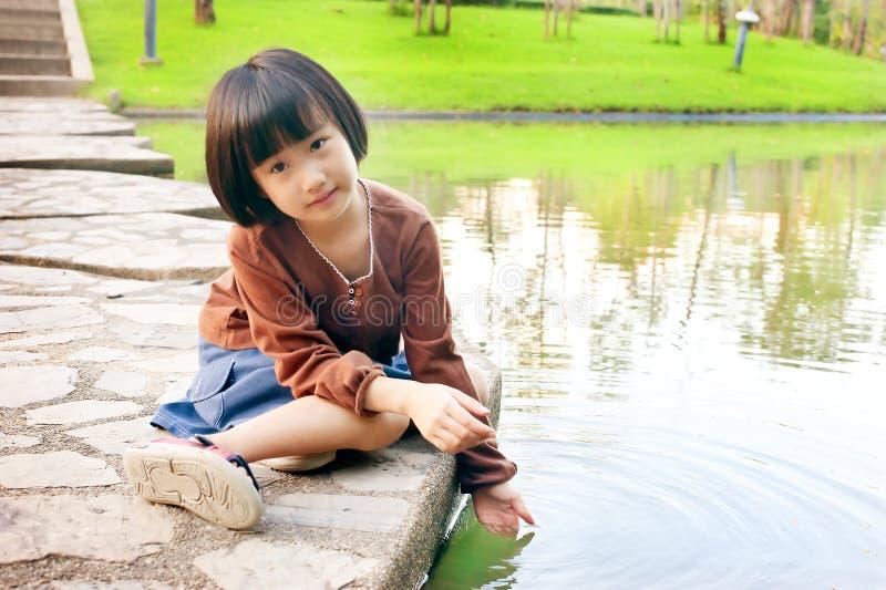 Petit enfant asiatique jouant sur l'eau du dock du lac photographie stock