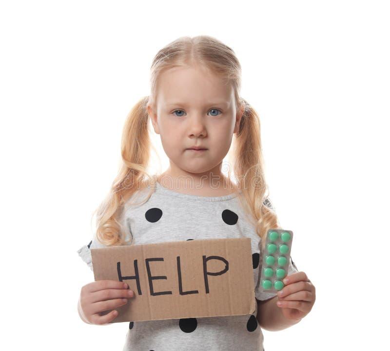 Petit enfant avec des pilules et aide de mot ?crite sur le carton Danger d'intoxication de m?dicament photographie stock libre de droits