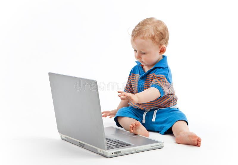 Petit enfant avec l'ordinateur portable photographie stock libre de droits