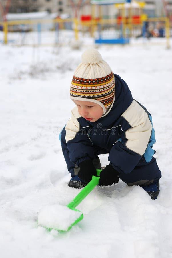 Petit enfant avec la pelle et la neige photos libres de droits