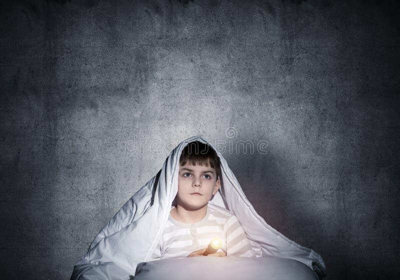 Petit enfant avec lampe de poche caché sous une couverture photos libres de droits