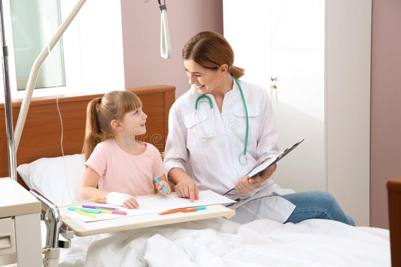 Petit enfant avec le dessin intraveineux d'égouttement dans le lit d'hôpital photo stock