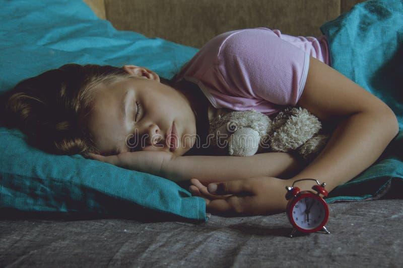 Petit enfant blond dormant dans son lit avec le jouet images libres de droits