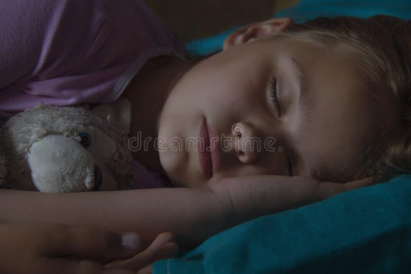 Petit enfant blond dormant dans son lit avec le jouet photographie stock