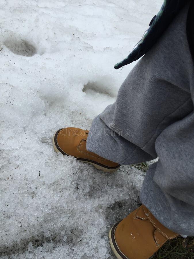 Petit enfant dans des bottes de travail jouant dans la neige photographie stock libre de droits