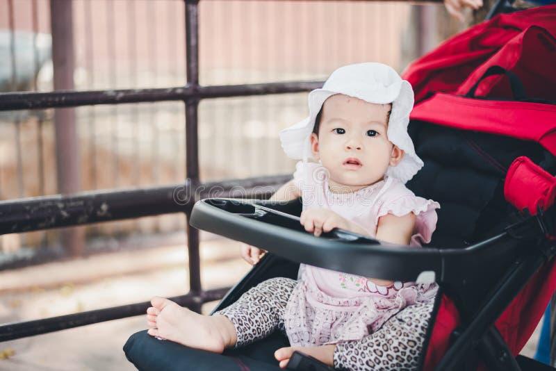 petit enfant de bébé avec le chapeau, se reposant dans la poussette à extérieur photo stock