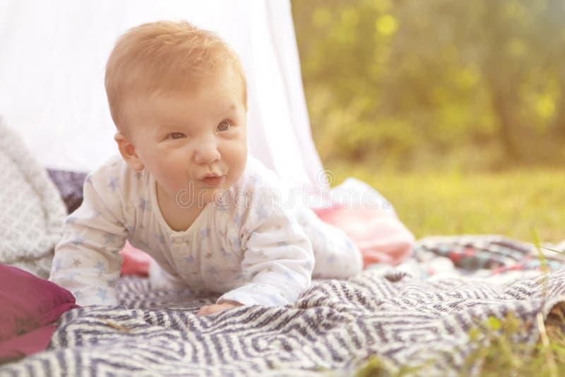 Petit enfant de bébé garçon de nourrisson nouveau-né sur un plaid en parc Été Su image stock