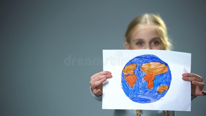 Petit enfant de sourire montrant l'image de la terre dans la cam?ra, concept global de paix image libre de droits