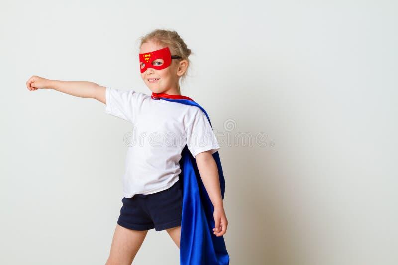 Petit enfant drôle de superhéros de puissance dans un imperméable rouge Concept de super héros photos libres de droits