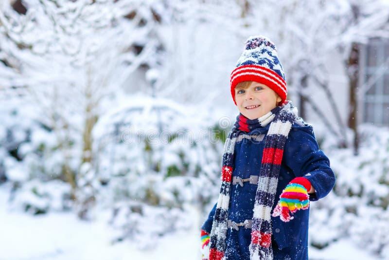 Petit enfant drôle mignon dans des vêtements colorés de mode d'hiver ayant l'amusement et jouant avec la neige, dehors pendant le image libre de droits
