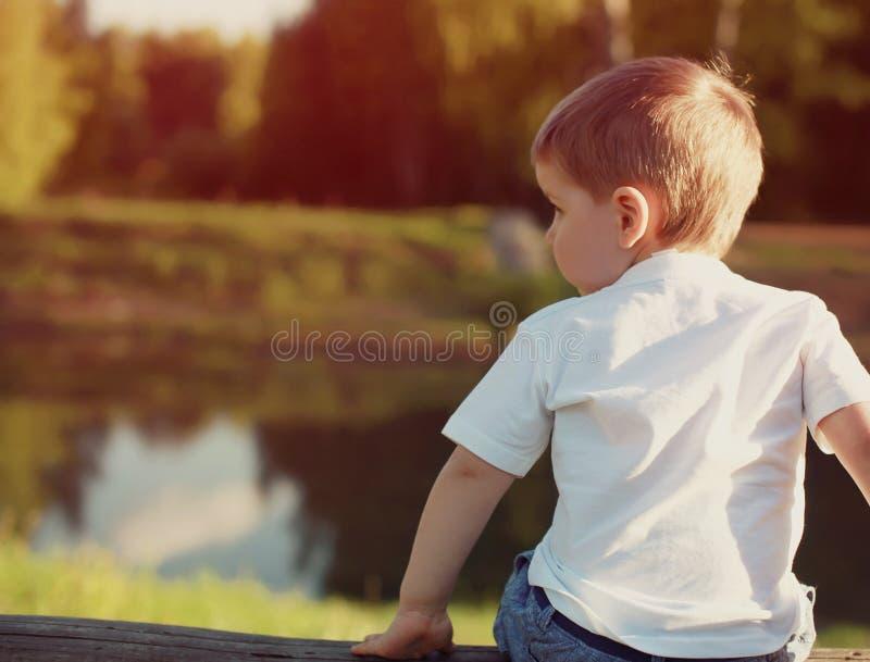 Petit enfant du regard songeur arrière loin image libre de droits
